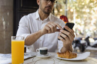 Businessman having breakfast in a cafe and using cell phone - MAUF01956