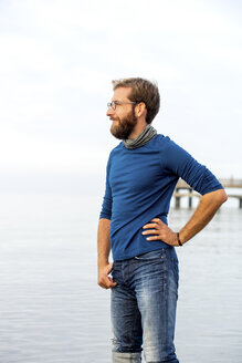 Germany, Rerik, bearded man in front of the sea looking at distance on hazy day - PUF01347