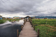 Footbridge by Inle Lake and field against cloudy sky - CAVF60349