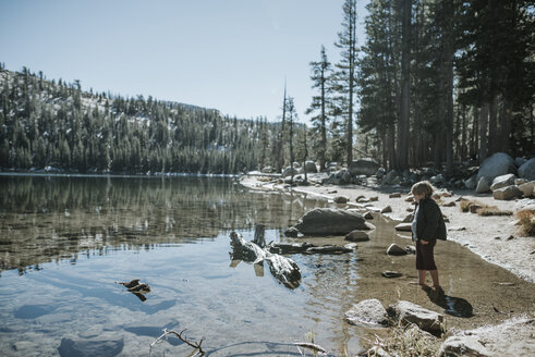 Side view of boy standing in lake during sunny day at Yosemite National Park - CAVF60427