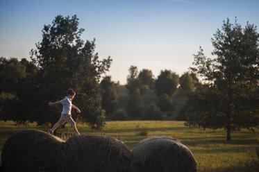 Playful boy walking on hay bales at field - CAVF60430
