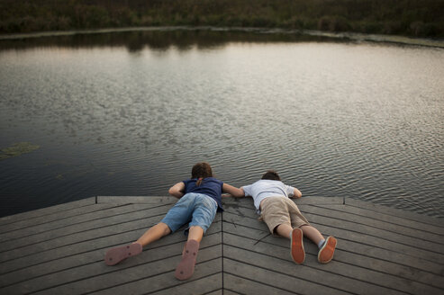 High angle view of carefree siblings lying on pier over lake at park - CAVF60433