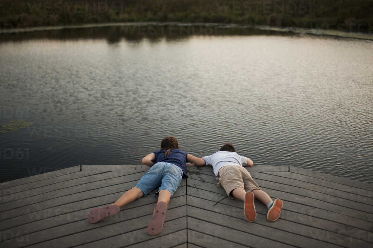 High angle view of carefree siblings lying on pier over lake at park - CAVF60433 - Cavan Images/Westend61