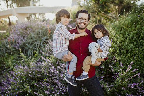 Portrait of father carrying sons while standing against plants at park - CAVF60472