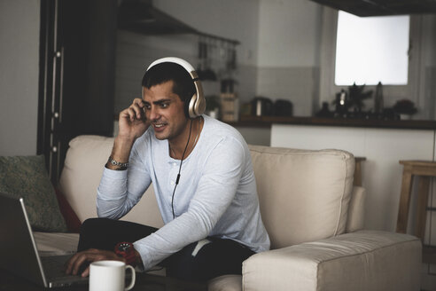 Smiling young man sitting on sofa at home wearing headphones and using laptop - ERRF00360