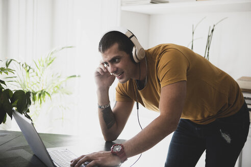Smiling young man wearing headphones and using laptop - ERRF00366