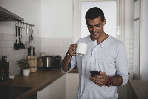 Smiling young man with cup of coffee using cell phone in kitchen at home - ERRF00369