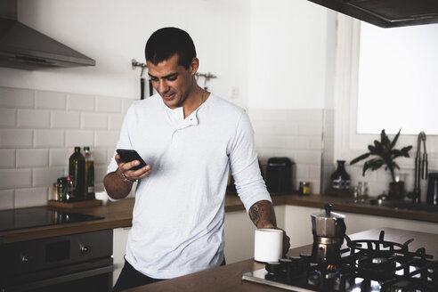 Smiling young man with cup of coffee using cell phone in kitchen at home - ERRF00372
