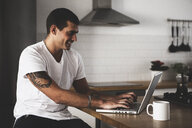 Smiling young man using laptop in kitchen at home - ERRF00387