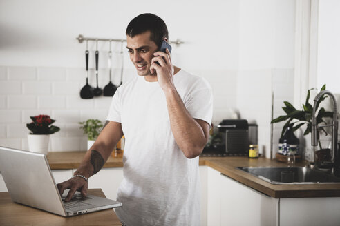 Smiling young man using laptop and cell phone in kitchen at home - ERRF00390