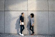 Two colleagues talking outdoors leaning against a wall - JRFF02192