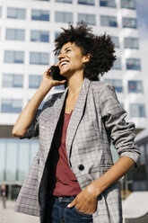 Laughing businesswoman on cell phone outside office building - JRFF02231