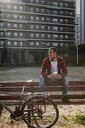 Young man sitting on a bench in the city next to bicycle - ERRF00406
