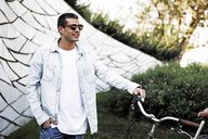 Young man with bicycle and sunglasses on the go - ERRF00412