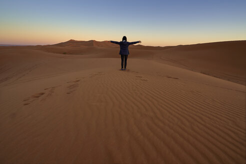 Morocco, back view of woman sitting on desert dune at twilight - EPF00507