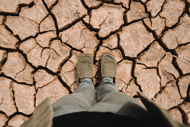 Low section of man standing at barren landscape - CAVF60489