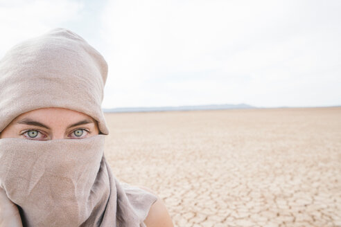 Portrait of woman wearing scarf standing at barren landscape against sky during sunny day - CAVF60492
