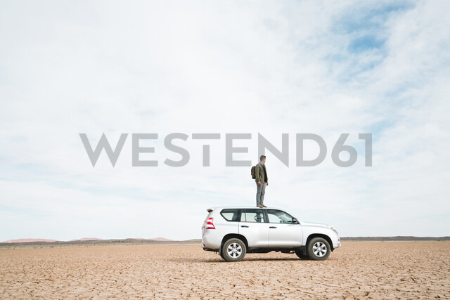 Side view of man standing on off-road vehicle at barren landscape against cloudy sky - CAVF60498 - Cavan Images/Westend61