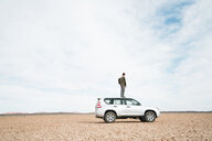 Side view of man standing on off-road vehicle at barren landscape against cloudy sky - CAVF60498