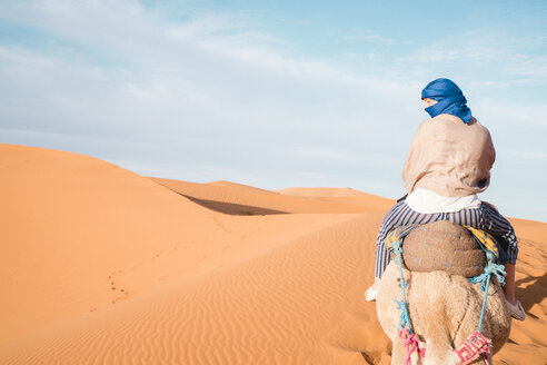 Rear view of woman wearing scarf riding camel at Merzouga desert against sky - CAVF60504