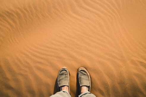 Low section of man standing on sand at Merzouga desert - CAVF60510