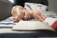 Boy reading picture book while lying on bed at home - CAVF60513