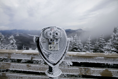 Frozen coin operated binoculars at observation point against mountains - CAVF60519