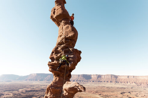 Female hikers climbing on rock formation against clear sky - CAVF60531