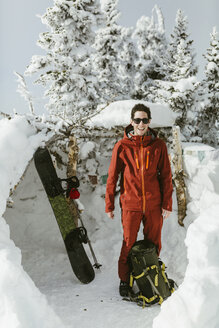 Full length of confident hiker wearing ski-wear while standing on snowy field - CAVF60600