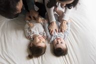 High angle view of playful parents tickling children on bed at home - CAVF60615