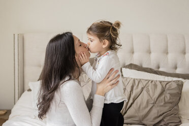 Loving mother and daughter kissing on mouth at home - CAVF60621