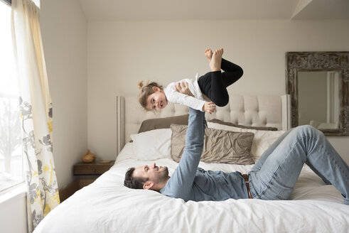Playful father lifting daughter while on bed at home - CAVF60624