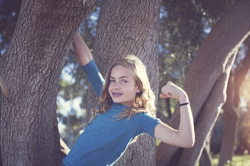 Portrait of confident girl flexing muscles while hanging on tree trunk at park - CAVF60630