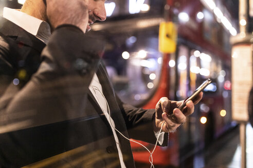 UK, London, businessman with cell phone and earbuds at the bus station by night - WPEF01194