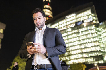 UK, London, businessman on the go checking his phone while commuting by night - WPEF01197