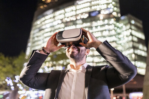 UK, London, businessman in the city wearing vr glasses by night - WPEF01200