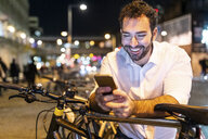UK, London, happy man looking at his phone by night - WPEF01203