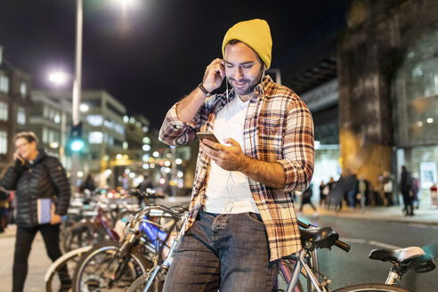 UK, London, man commuting at night in the city and looking at his phone - WPEF01209