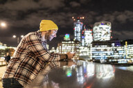 UK, London, smiling man leaning on a railing and looking at his phone with city lights in background - WPEF01215