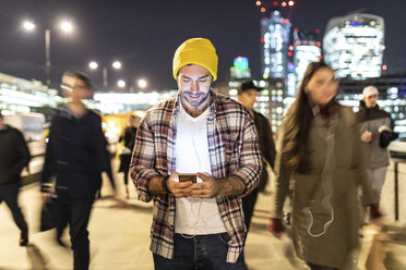 UK, London, smiling man looking at his phone by night with blurred people passing nearby - WPEF01218