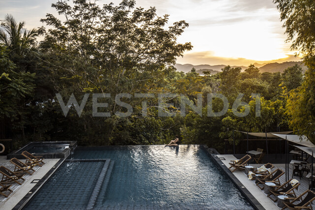 Philippines, Palawan, Coron, woman sitting at swimming pool in the evening - DAWF00766 - Daniel Waschnig Photography/Westend61