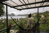 Philippines, Palawan, El Nido, woman on terrace with hammock - DAWF00772