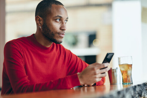 Pensive young man wearing red pullover at counter of a bar with soft drink and mobile phone - JSMF00698