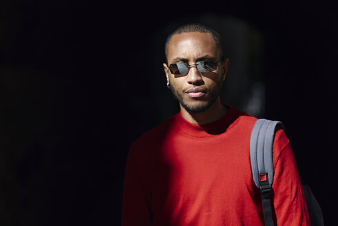 Portrait of young man wearing sunglasses and red pullover - JSMF00701
