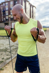 Muscular man exercising with expander outdoors - MGOF03845