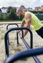Muscular man exercising outdoors - MGOF03848