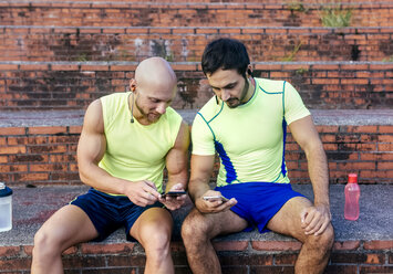 Two athletes sharing smartphones after workout - MGOF03851