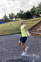 Muscular man skipping rope outdoors - MGOF03854