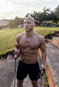 Barechested muscular man exercising with expander outdoors - MGOF03875
