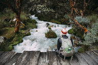 Peru, Huaraz, Man with woolly hat and backpack sitting on wooden bridge at a river - GEMF02694